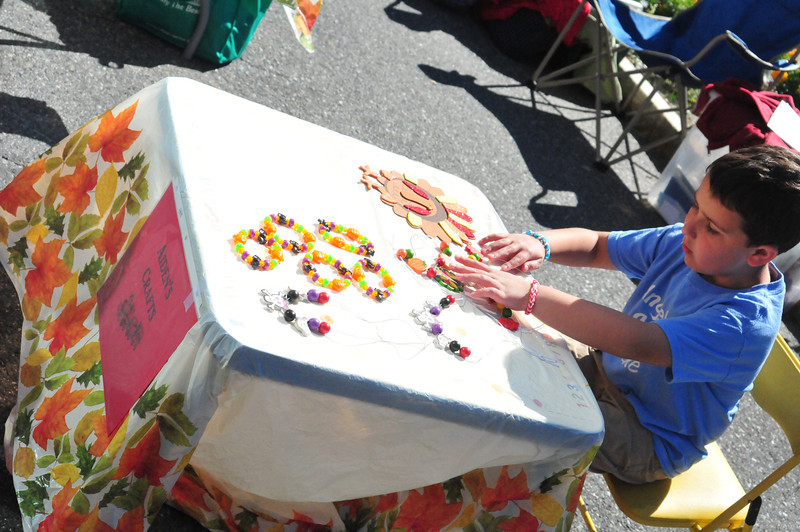 Aiden Deane, 7, creates a necklace a craft table during the annual Autumn Arts and Crafts Fair, part of the Fall Foliage Festival, on Main Street in North Adams onSunday September 29, 2013. \<br />  (Sarah Howard/Special to the Transcript)
