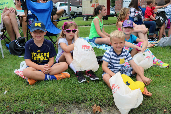 SHERRY VAN ARSDALL | THE GOSHEN NEWS A group of cousins wait with bags to gather candy for  2016 Bristol Homecoming Parade Saturday. From left, Cohen Davis, 7, Claire Parker, 6, Max Davis, 4, and Charli Parker, 7.