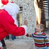 Joey Diaz, as Santa Claus, high fives Sam Brenneman, 4, in Goshen Sunday.