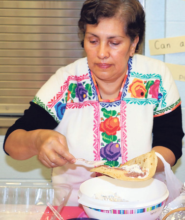 SHERRY VAN ARSDALL | THE GOSHEN NEWS Maria Guadalupe Gasper serves baleadas, an Honduran dish, during an Hispanic Heritage Celebration at Chandler Elementary School Saturday.