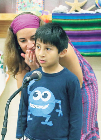 SHERRY VAN ARSDALL | THE GOSHEN NEWS Chandler Elementary School kindergartner Kirk Juarez welcomes parents and students in Spanish with some coaching by his teacher Erin Behan Morillo during an Hispanic Heritage Celebration at the school Saturday.
