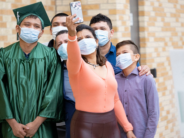 Concord Senior Axel Pineda, left, and his family take a selfie while waiting outside to walk the stage at Concord High School during graduation Monday morning.