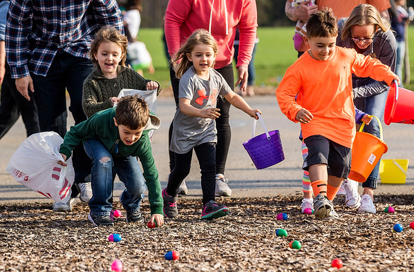 JAY YOUNG | THE GOSHEN NEWS<br /> Six-year-old Abram Mehl races forward to scoop up an egg as his sister, Eden, 4, both of New Paris, follows close behind while Olive Steffen, 4, and her brother Kingston, 5, both of New Paris, rush forward after their own eggs during an Easter egg hunt Saturday morning at New Paris Elementary School. The egg hunt was sponsored by the New Paris Lions Club and contained 4,000 eggs.