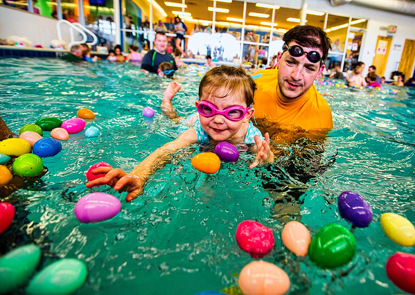 JAY YOUNG | THE GOSHEN NEWS<br /> Two-year-old Grace Davis reaches for an egg while father Willie, both of Bristol, holds her afloat in the water as they participate in the second annual Easter egg hunt at Shepard Swim School in Elkhart.
