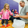 JAY YOUNG | THE GOSHEN NEWS<br /> Three-year-old Lyla Hinkle sorts through her bag of goodies with some help from her dad, Tom, both of New Paris during an Easter egg hunt Saturday morning at New Paris Elementary School. The egg hunt was sponsored by the New Paris Lions Club and contained 4,000 eggs.