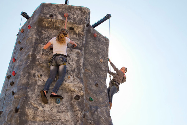 SAM HOUSEHOLDER | THE GOSHEN NEWS<br /> Bestinee Bornkamp, 12, left, and her friend Cierra Thomas, 9, talk while climbing a rock wall at the Wakarusa Maple Syrup Festival Saturday. It was the 45th annual event and for the first time it will run through Sunday.