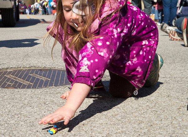 SAM HOUSEHOLDER | THE GOSHEN NEWS<br /> Clara Yoder, 7, of Wakarusa, reaches for a piece of bubble gum during the Maple Syrup Festival parade Saturday. Organizers expected a successful event because of the nice weather scheduled for the three day event.