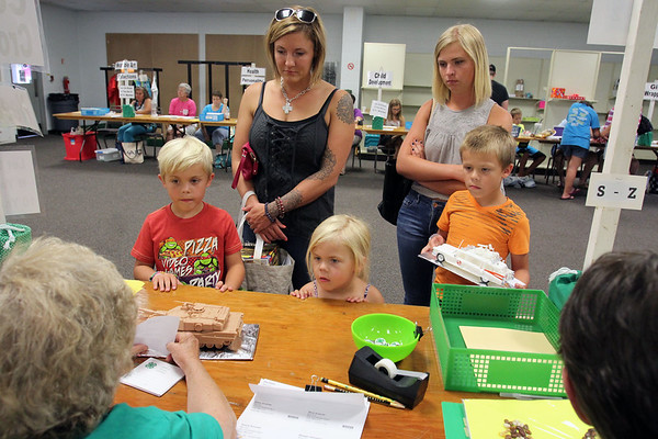 JULIE CROTHERS BEER | THE GOSHEN NEWS<br /> Mark Scearse, 8, left, and his brother Ethan, 7, right, check in their model projects for Mini 4-H during Elkhart County 4-H Fair check in Monday. With them are Adilyn, 4, Jennifer Scearse and Hannah Scearse. Project check in took place from 11 a.m. to 7 p.m. Monday with all ages stopping by the fairgrounds to drop off their completed projects. The projected will be judged and ribbons awarded in the coming days leading up to the start of the 2016 fair Friday.
