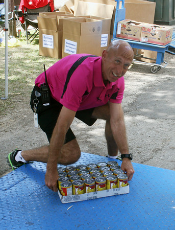 "SHERRY VAN ARSDALL | THE GOSHEN NEWS<br /> Tim Yoder, Elkhart County 4-H Fair President, puts down the last case of food to be weighed for the ""All IN"" food drive for attempting a ""Guinness Book of World Records"" for the largest single-day food drive."