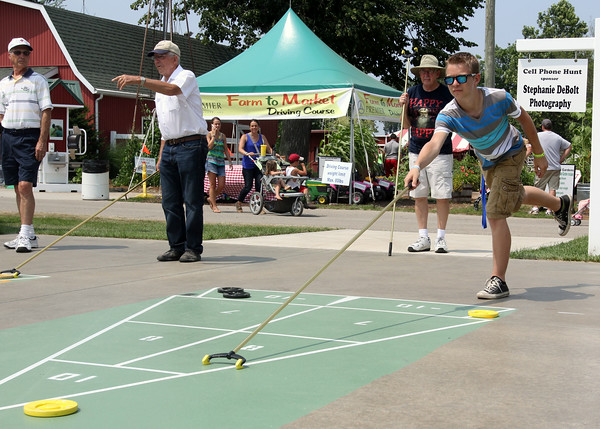 JULIE CROTHERS | THE GOSHEN NEWS<br /> Curtis Nisley, of Goshen, pushes his puck across the shuffleboard court Tuesday during an afternoon competition at the Elkhart County 4-H Fair.