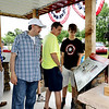SHEILA SELMAN | THE GOSHEN NEWS<br /> From left, Steve Jackson, Elkhart, Rob jackson, Goshen, and Bryan Jackson, Elkhart, look at one of four panels at the Lincoln Highway Association pavilion at Fidler Pond Park Saturday. Steve and Rob Jackson said their parents, who live in Columbus, Ohio, are part of the National Lincoln Highway Association. The bought an RV trailer in Elkhart and drove the entire length of the highway, which runs from New York to San Francisco.