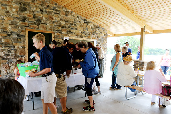 SHEILA SELMAN | THE GOSHEN NEWS<br /> People line up to grab snacks and drinks inside Chiddister Pavilion following the dedication of Fidler Pond Park Saturday in Goshen.