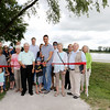 SHEILA SELMAN | THE GOSHEN NEWS<br /> City and park officials join private donors in cutting the ribbon at the dedication of Fidler Pond Park in Goshen Saturday morning. In front, cutting the ribbon, are John Fidler, Ethan Kupke, Goshen Mayor Jeremy Stutsman, Rochelle M. Chiddister and Donald R. Chiddister. Behind them are Kaelyn Webb, Olivia Webb, Collette Webb Kelley Fidler, Sara and Jack Kupke and two more of their children, Mason and Harrison, Shelly Fidler, Brad Webb, Lois Fidler, Doug Wogoman and Margie Zentz (Wayne Wogoman's son and daughter), Park Baord member Jim Wellington, Parks Superintendent Sheri Howland, and Park Board member Barb Swartley.