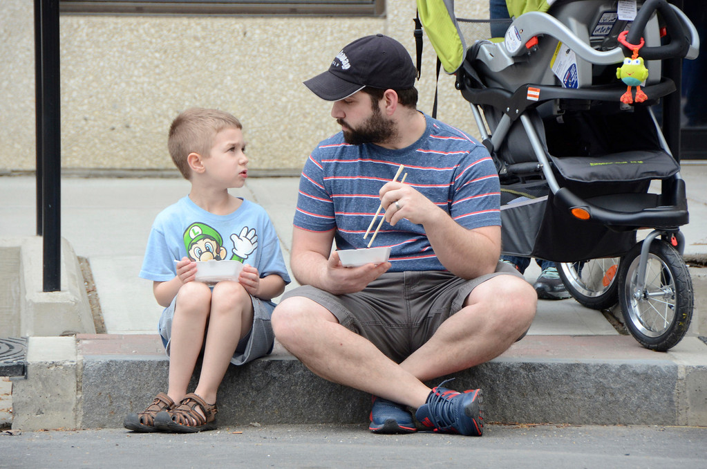 . Ace Coviello, 6, eats some dumplings while his dad, Mark, eats some sushi from Shiro, on North Street in Pittsfield during the first Third Thursday of the season on May 15, 2014. Gillian Jones / Berkshire Eagle Staff / photos.berkshireeagle.com