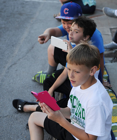HALEY WARD | THE GOSHEN NEWS<br /> Kamrin Lewis, Christian Boyd and Wesley Bachman from Elkhart watch as cars drive down Main Street during First Fridays Cruisin' Reunion on Friday. They said they favored the GT-R and the Porche.