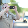 HALEY WARD | THE GOSHEN NEWS<br /> Chris Shakley takes a photo of a car during First Fridays Cruisin' Reunion on Friday on Main Street. Shakley went to Goshen High School, graduating in 1984, and he remembers driving his 1968 Ford Tourneo before the event was shut down.