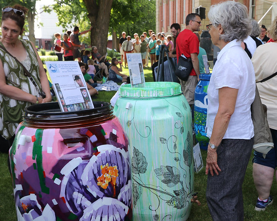 SHERRY VAN ARSDALL | THE GOSHEN NEWS<br /> Phyllis Stutzman of Goshen looks at rain barrels decorated for the auction during the 8th annual rain barrel auction during June First Fridays Sweet Summer Kick-off in downtown Goshen.