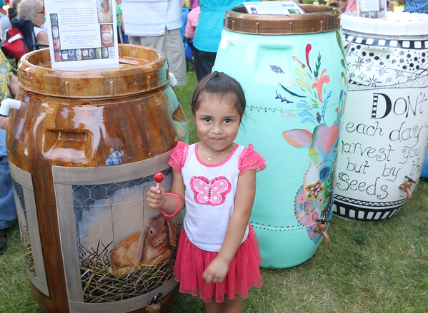 "SHERRY VAN ARSDALL | THE GOSHEN NEWS<br /> Four-year-old Angelique Hernandez grinS as she ate her sucker near a barrel with rabbits, titled ""Hare we are!"" during the 8th annual rain barrel auction during June First Fridays Sweet Summer Kick-off in downtown Goshen."