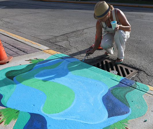 "SHERRY VAN ARSDALL | THE GOSHEN NEWS<br /> Artist Leah Borden puts the finishing touches on a painted storm drain for the ""Storm Drain Art Project"" at S. Fifth and E. Washington streets in Goshen. There are eight painted storm drains as a way to share the message to protect local waters by keeping these drains free from pollutants. All stormwater in Goshen ends up in the Elkhart River, either directly, piped or through the wastewater treatment plant. That means verything dropping on the roads, parking lots or piped into a storm drain may pollute the river."
