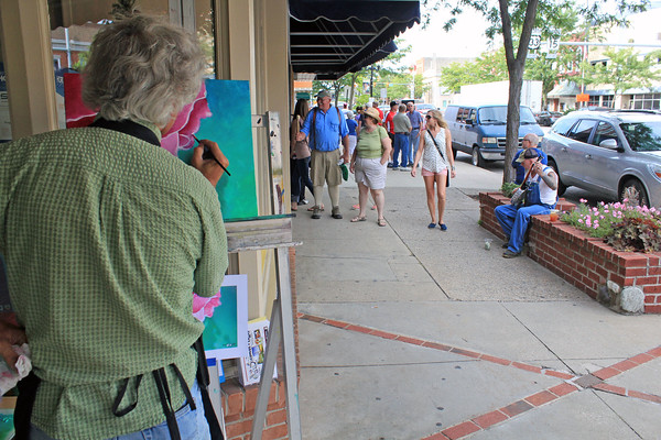 Roger Schneider | The Goshen News<br /> ARTIST RICH HOOTON paints on a canvas during First Fridays while in the background John Muday plays the banjo for tips. A variety of street activities occurred during the monthly event.