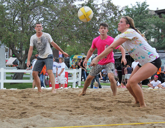 Roger Schneider | The Goshen News<br /> ALLI CARITHERS returns a shot during volleyball competition Friday night in downtown Goshen. At left is Willis Schwartz and at right is Gabriel Schlabach.