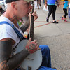 Roger Schneider | The Goshen News<br /> JOHN MUDAY plays the banjo for tips while sitting on a bench along Main Street Friday night during First Fridays.