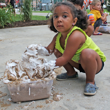 Roger Schneider | The Goshen News<br /> AUBREY BULLEN digs into a mixture of sand and shaving cream to have some fun at First Fridays Friday night in downtown Goshen.