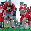 Haley Ward | The Goshen News<br /> Carter Wirth touches the new artificial turf surface that now covers Foreman Field as his Junior Football League teammates gather nearby.