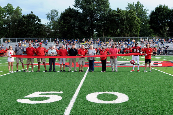 Haley Ward | The Goshen News<br /> A 12-foot red ribbon was held by Goshen Community Corporation school officials, representatives of The Motz Group, of Cincinnati, Ohio, past and current football coaches, and GHS football, band and cheerleader students during a ribbon-cutting ceremony to celebrate the new artificial turf covering Foreman Field before the first football game of the year Friday night