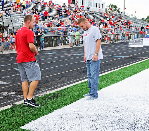 Haley Ward | The Goshen News<br /> Brian Gross, left, and Ryan Whalen, both Goshen High School alumni, take a look at the new artificial turf covering Foreman Field before the first football game of the year Friday night.