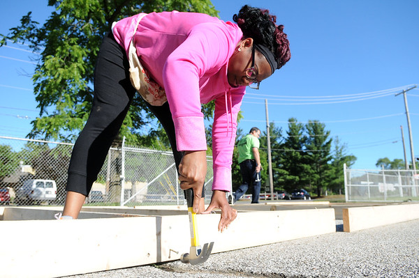 "HALEY WARD | THE GOSHEN NEWS<br /> Toya Sheppard drives a nail into the frame for the siding of her new house during a build for Habitat for Humanity of Elkhart County on Wednesday at a Robert Weed Plywood parking lot in Bristol. ""I've been waiting for this a long time,"" Sheppard said. ""My kids are all out here and we're having a good time."""