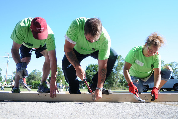 HALEY WARD | THE GOSHEN NEWS<br /> Bruce Kotek, Bryan Courtney and Miranda Starks hammer during a build for Habitat for Humanity of Elkhart County on Wednesday at a Robert Weed Plywood parking lot in Bristol. Volunteers built the house for Toya Sheppard and her three children Genice Crawford, Genoris Crawford and Angell Sheppard. They were all present at the build.