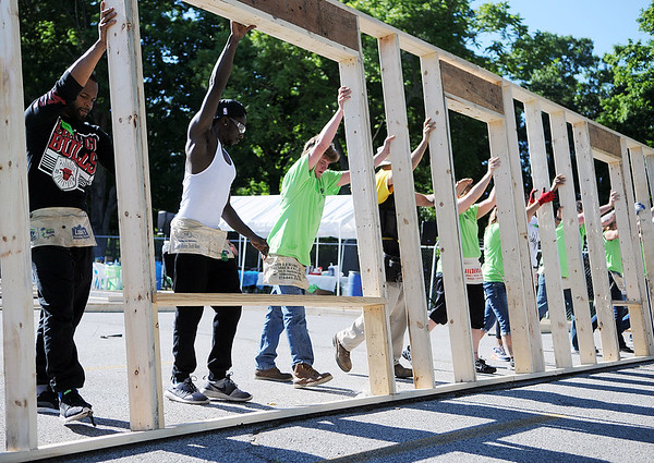 HALEY WARD   THE GOSHEN NEWS<br /> Volunteers raise one of the exterior walls during a build for Habitat for Humanity of Elkhart County on Wednesday at a Robert Weed Plywood parking lot in Bristol. This was the first time Habitat for Humanity of Elkhart County has raised the walls in a parking lot.