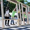 HALEY WARD | THE GOSHEN NEWS<br /> Volunteers raise one of the exterior walls during a build for Habitat for Humanity of Elkhart County on Wednesday at a Robert Weed Plywood parking lot in Bristol. This was the first time Habitat for Humanity of Elkhart County has raised the walls in a parking lot.