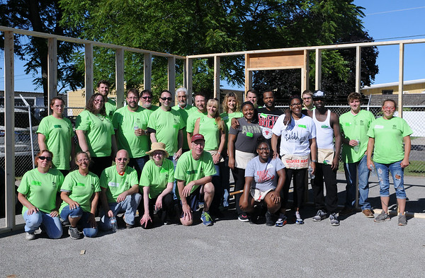 HALEY WARD | THE GOSHEN NEWS<br /> The volunteers with Robert Weed Plywood stand with the family who's receiving the house during a Habitat for Humanity build for Elkhart County on Wednesday at a Robert Weed Plywood parking lot in Bristol.