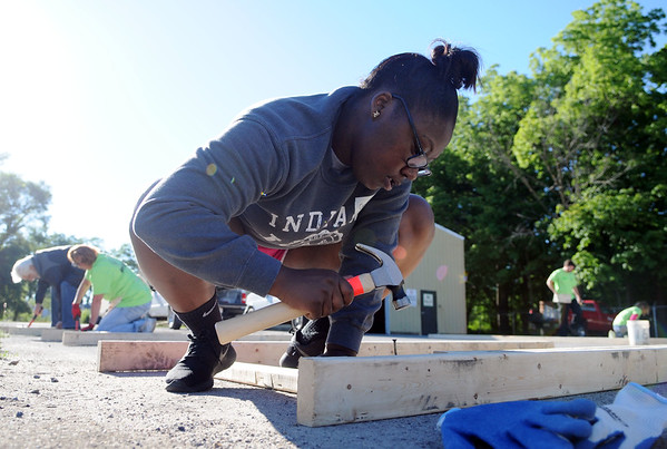HALEY WARD | THE GOSHEN NEWS<br /> Genice Crawford, 20, drives a nail into the framing of a door for her mom's new house during a build for Habitat for Humanity of Elkhart County on Wednesday at a Robert Weed Plywood parking lot in Bristol.