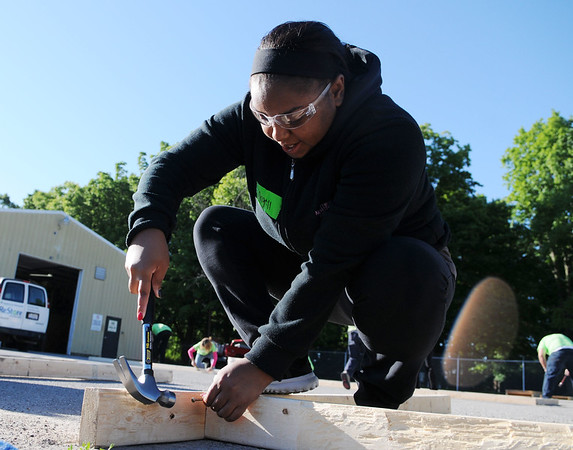 HALEY WARD | THE GOSHEN NEWS<br /> Angell Sheppard, 18, drives a nail into the framing of a door for her mom's new house during a build for Habitat for Humanity of Elkhart County on Wednesday at a Robert Weed Plywood parking lot in Bristol. Sheppard said she struggled with using the hammer, but volunteers showed best to do it.