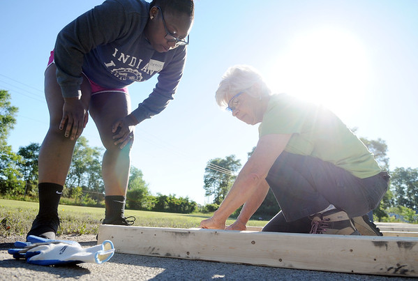 HALEY WARD   THE GOSHEN NEWS<br /> Genice Crawford looks over Molly Prime, volunteer coordinator with Habitat for Humanity, while building the door frame during the build on Wednesday at a parking lot in Bristol. Crawford was helping build the home for her mom Toya Sheppard.