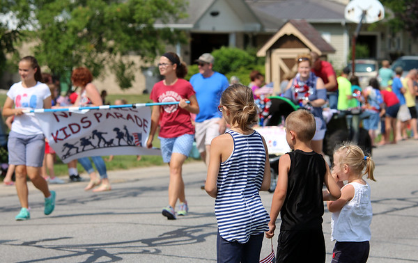 JULIE CROTHERS BEER | THE GOSHEN NEWS<br /> Lizzy, 8, George, 6, and Caroline Hertsel, 3, watch as the Nappanee Independence Day parade passes them on East Woodview Drive Tuesday morning.