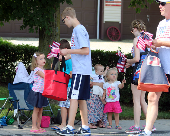 JULIE CROTHERS BEER | THE GOSHEN NEWS <br /> At left, Adalynn Yoder, 4, accepts an American flag from a parade participant Tuesday in Nappanee. Her siblings, Jacob, 6, Emily, 2, and Megan, 7 months, also enjoyed the parade with their parents Derek and Trisha Yoder of Goshen.