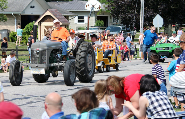 JULIE CROTHERS BEER   THE GOSHEN NEWS<br /> Parade participants wave to the crowd as they drive by on East Woodview Drive during the Independence Day parade Tuesday in Nappanee.