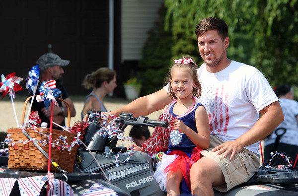 JULIE CROTHERS BEER | THE GOSHEN NEWS<br /> Bailey Beehler, 6, of Nappanee rides in the Nappanee Independence Day parade Tuesday with her uncle Nick Graber.