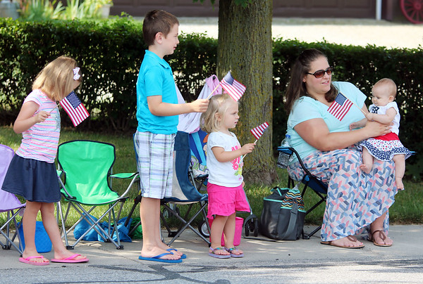 JULIE CROTHERS BEER   THE GOSHEN NEWS<br /> With American flags at the ready, Adalynn, 4, Jacob, 6, Emily, 2, and Megan, 7 months, watch the Nappanee Independence Day parade Tuesday with their mom Trisha Yoder and dad Derek (not pictured). The Goshen family decided to drive over for Tuesday morning's parade.