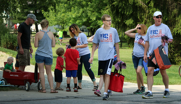 JULIE CROTHERS BEER   THE GOSHEN NEWS<br /> Parade participants hand out American flags during the event Tuesday in Nappanee.