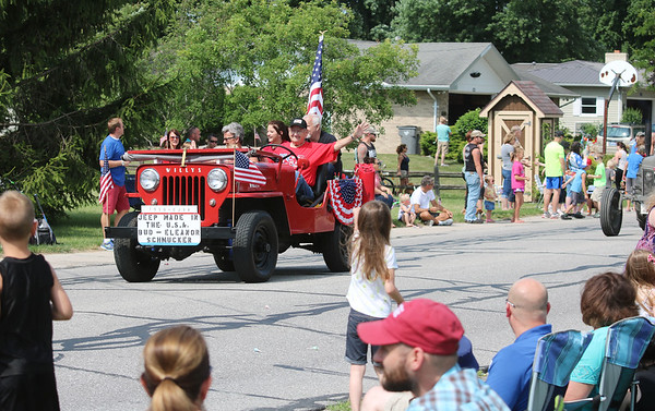 JULIE CROTHERS BEER | THE GOSHEN NEWS<br /> Parade participants wave to the crowd as they drive by on East Woodview Drive during the Independence Day parade Tuesday in Nappanee.