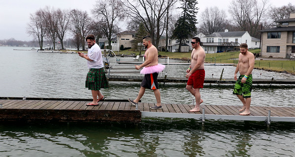 JULIE CROTHERS BEER | THE GOSHEN NEWS<br /> Participants walk down the dock before jumping into Simonton Lake during the 12th annual Leprechaun Leap Saturday, March 18. The annual event benefits United Cancer Services of Elkhart County.