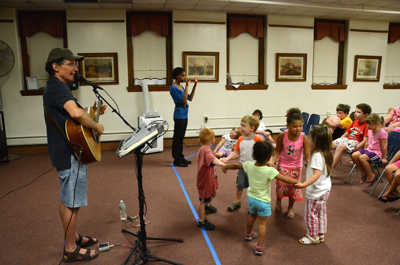 Children dance to music at the Adams Free Library on Tuesday July 30, 2013 during a performance by Tom Sieling of Newfield, NY entitled 'Howl at the Moon.' The musical presentation was sponsored by the library's summer reading program which is themed, 'Dig into Reading.' (Gillian Jones/North Adams Transcript)