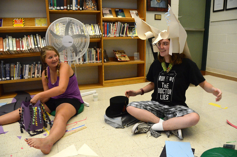 Using no tape or glue, kids make paper masks during a workshop with artist Ann Kremers at the Williamstown Public Library on Thursday July 18, 2013. At left, Kate Bernardy, 13, of Williamstown looks at, Olivia Kipp, 17, of Hancock as she wears a mask she made of a mouse.(Gillian Jones/North Adams Transcript)