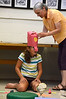 Using no tape or glue, kids make paper masks during a workshop with artist Ann Kremers, right, at the Williamstown Public Library on Thursday July 18, 2013. Grace Sanchez, 11, of Williamstown gets her mask inspected by Kremers. (Gillian Jones/North Adams Transcript)