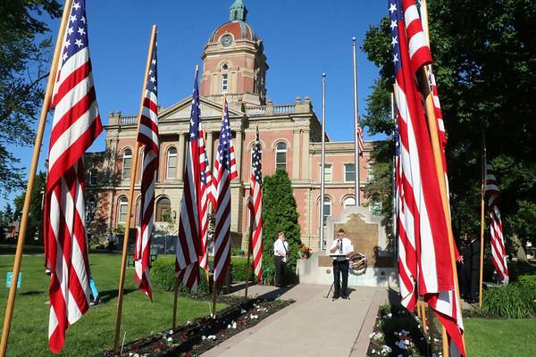 SHEILA SELMAN | THE GOSHEN NEWS<br /> Veterans conduct a memorial service at the Elkhart County War Memorial in front of the Elkhart County Courthouse Monday.